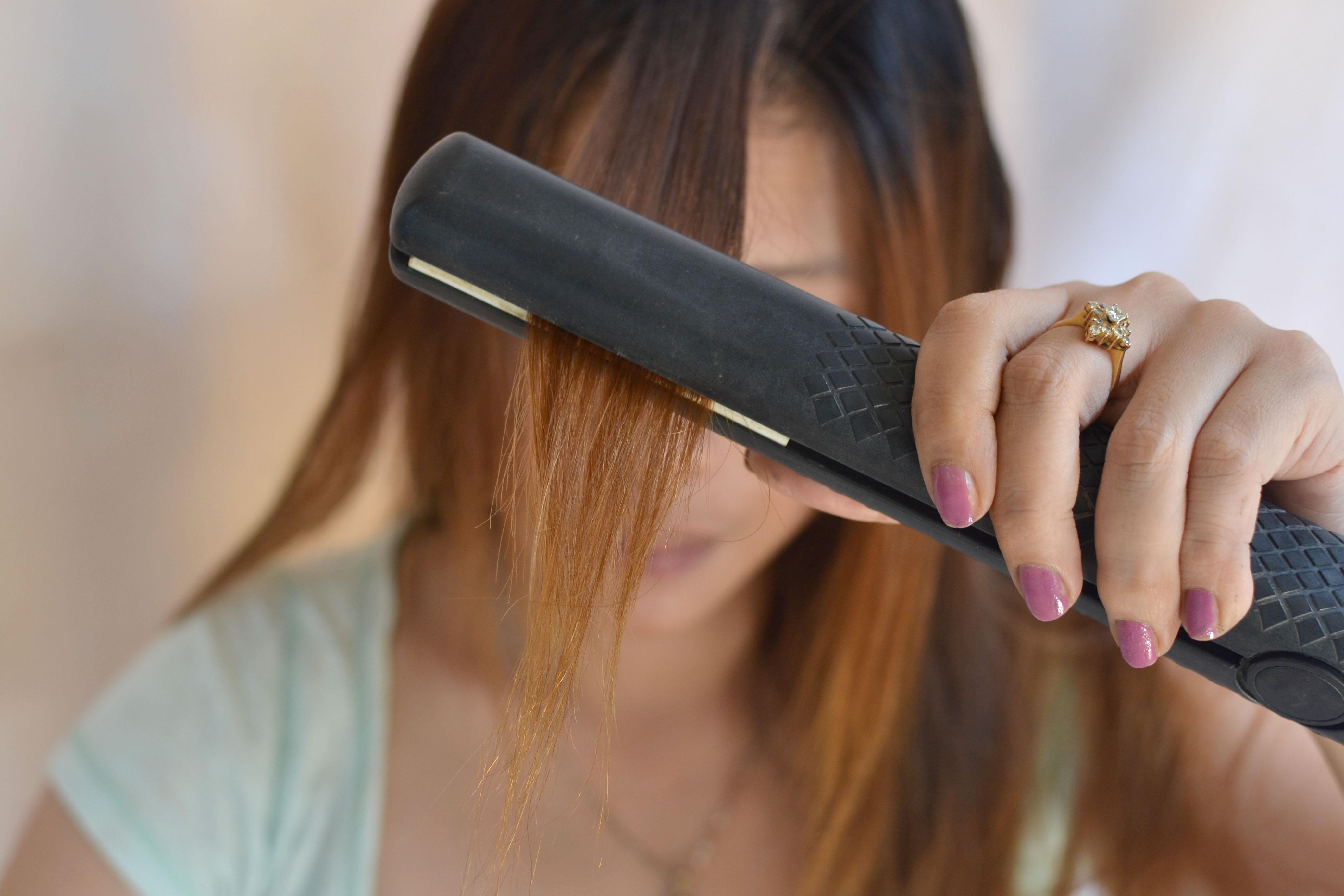 Процесс выпрямления волос утюжком